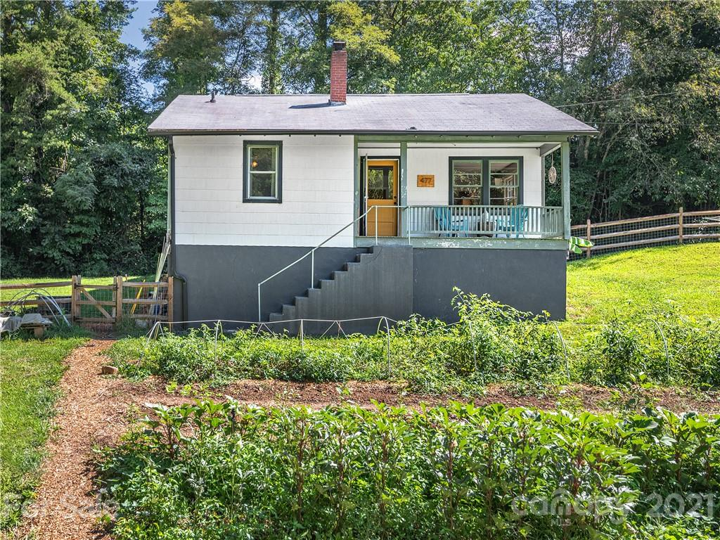 Bring your chickens! Whether you are looking to take respite in a rural setting or live off the land, this home has got it all! This sweet 2 bedroom, 1 bathroom bungalow offers all the classic charm of country living while also being a fully operational farmstead. Let your dogs, chickens, and animals roam around the fully fenced-in front yard or take advantage of the established garden beds and live off the land. Original hardwoods throughout, radiant heated kitchen floors, and a high-efficiency MORSØ woodstove make this bungalow extra cozy. The open and bright kitchen offers ample cabinet space and a kitchen pass-through for easy access to the living room. Thoughtfully updated with new double pane windows, well pump and tank, Mitsubishi Mini-split, gutters, and expansive split-rail fence. Conveniently located within 10 minutes of Leicester and Weaverville and only 20 minutes to West Asheville restaurants and shops!
