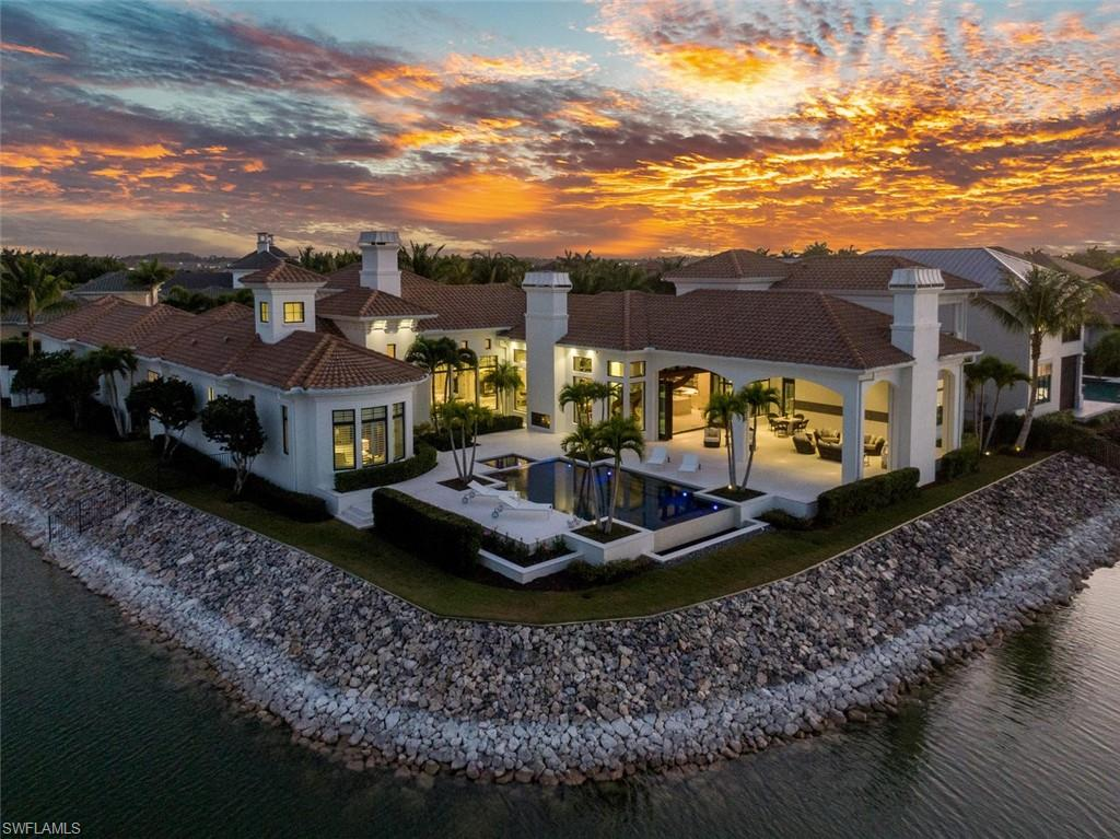 Perfectly situated on a highly desirable private corner peninsula lot, this distinctive estate home combines inspiration from Miromar's rich lifestyle with an elegant modern point of view. Sweeping waterfront views and an open concept design furnished with sophisticated architectural elements create a dreamy setting ideal for entertaining. The outdoor oasis features an infinity pool, fireplace, picturesque wrap around views and a private boat dock. The stylish open chef's kitchen is a foodie's delight with ample storage that has been gracefully enclosed in custom 2-tone cabinetry. A dramatic winding staircase leads from the great room to a full guest suite with a balcony and a 2nd home office. Modern lighting further highlights the beauty of this incredible lakeside retreat fully equipped with every lifestyle convenience including 4 car ports, electric hurricane shutters, screens under the lanai and a generator. Owners enjoy an expansive amenity suite including 700-acres of freshwater lakes, 3 miles of white sand beaches, spa & fitness center, concierge service, Clubhouse, Blue Water Beach Grill, and optional membership to Arthur Hills Signature Championship golf course.