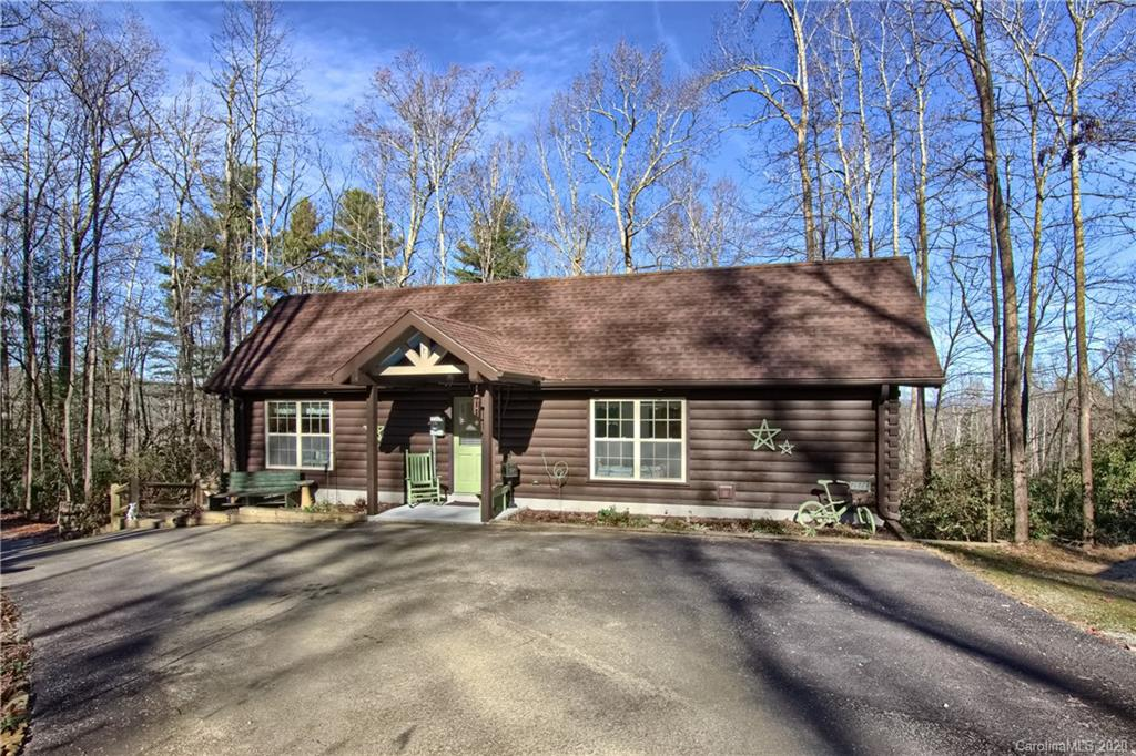 This lovely custom log home sits on 2.34 acres of private and wooded land providing beautiful long range views and the peaceful sounds of the seasonal stream from your covered wrap-around deck. Inside enjoy the open floor plan with essentially two masters and bonus room for office/den or 3rd bedroom. Granite countertops in kitchen and baths. Private well with 4-bedroom septic. Basement has stand-up space for Workshop and/or Storage. There is even a fenced relief area for pets! Detached custom 2-car carport. Paved frontage and easy access makes suitable for Permanent Residence or Seasonal Getaway or Rental Property. Located just minutes from downtown Hendersonville and DuPont State Recreational Forest - enjoy hiking, biking, fishing, horseback riding, waterfalls all year round! ATT Internet Service Available.