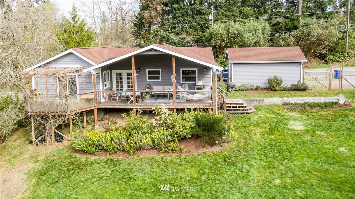 Conveniently located and easy to live in: This south facing, 2 bed 2 bath home features an open, chic main living area, framed by a large covered deck, all overlooking a pastoral fenced-yard, and forest. French doors, hardwood floors, and a large en-suite bedroom pair well with the comfort and convenience of living at the Island's center. The detached outbuilding hosts a convenient guest space or mother in law. The property is located in a vibrant neighborhood, connected to busses, and adjacent to Schools, the Roasterie, and the Arts Center. Great opportunity to enter the market, or have as an investment on Vashon Island.