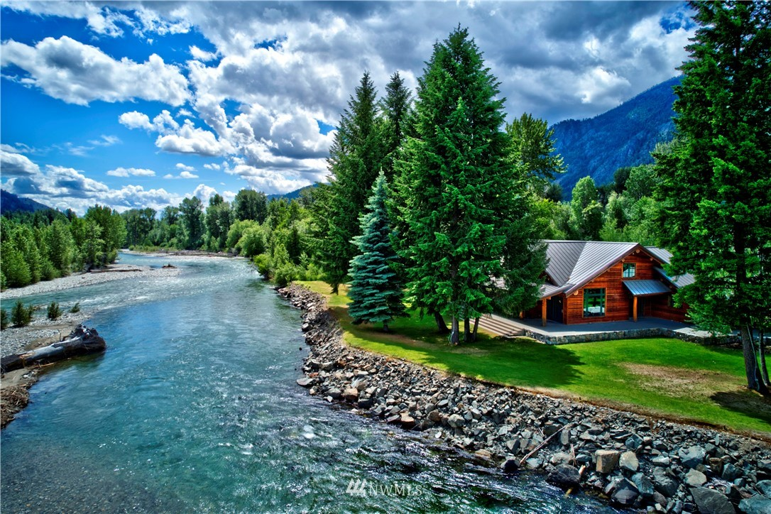 MAZAMA: Exceptional riverfront home on the Methow River. Spectacular views of the river & mountains from every window. This master piece is nestled on the rivers edge, surrounded w/ aspen & evergreens making it completely private. Featuring 36 acres, irrigated meadow, year-round creek, direct access to the community trail (trail passes included), borders State Land and 700' riverfront. An elegantly appointed two-story home, log beam accents, a huge hand crafted river-rock fireplace, radiant wood floors, gourmet kitchen, spacious open living/dining room, 3 bedroom suites w/ private bathrooms. Master suite w/ French doors onto the patio & river view.  Grand entry, rock patio and wainscoting, irrigation system.