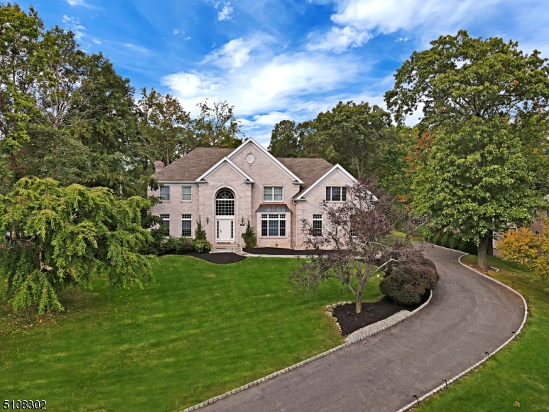 A majestic hillside setting for this elegantly appointed 6BR brick front colonial.  Located in prestigious Stone Ridge Estates, discerning buyers will appreciate all this home has to offer including a 2-story foyer, hardwood floors throughout, and spacious light-filled rooms.  The formal living and dining rooms boast crown molding, recessed lighting, and hardwood floors with border inlay.  The kitchen has everything you need to experience the joy of cooking! Stainless steel appliances include double ovens, a side-by-side refrigerator, dishwasher, and gas cooktop.  The large center island with seating area is perfect for an impromptu meal.  Just off the kitchen dining area, sliding doors open onto a deck that overlooks the expansive tree-lined backyard.  The family room features a fireplace, crown molding, and recessed lights.  A bedroom on the 1st floor with full bath lends itself to a possible in-law/au pair suite.  The main level laundry is a real convenience. The 2nd floor offers an impressive Master Bedroom suite highlighted by a tray ceiling, and arched doorway leading to a sitting room. The en suite master bath offers a skylight, jetted tub, dual sink vanity and over-sized shower with frameless shower door.  2 BRs share a Jack & Jill bath, and 2 BRs share a hall bath.  The finished lower level offers a wet bar, workout room, full bath, and possible office space. Set on nearly 1 acre, the property would lend itself to a pool for summer enjoyment.