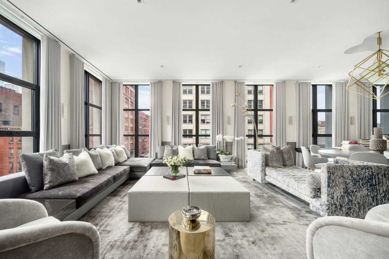 One of a kind, intelligently designed and sprawling 4,912 SF, this 4 bedroom corner home with children's playroom and home office/media room features tremendous scale and sophistication. It is highlighted by 27 floor to ceiling windows, 11 foot ceilings and 3 fireplaces located on one of Tribeca's most well regarded blocks with southern and western views.   As one enters the home through its large foyer with walk-in coat closet, they are struck with the scale of this light filled, nearly city block long apartment.  The informal living room, one of three distinct public spaces in the apartment, features a custom Smallbone kitchen with Iceberg White Calcite Brazilian full slab marble counters and backsplash and Miele appliances that overlooks the 58 foot long great room featuring 12 of the floor to ceiling windows with views of One World Trade, 56 Leonard and the charming cobblestone streets of Tribeca. At the northern end of this great room is a wet bar and one of the 3 fireplaces which creates an intimate atmosphere, while the generous southern side of the great room is perfect for comfortable day to day informal use.   The Eastern wing features an enormous 28 foot, south facing master suite with 4 windows overlooking quiet N Moore with views of the Freedom Tower, a fireplace, dual custom outfitted dressing rooms, and a five fixture bath with custom WetStyle vanity and Robern medicine cabinets.  The warm and atmospheric office/media room, which can be accessed through the master suite or a separate door, has the third fireplace, floor-to-ceiling built-ins with two work-at-home office stations and a recessed ceiling with a light bay.   The northern wing of the property features a children's playroom, 3 bedrooms with en-suite bathrooms including a guest suite with a washer/dryer separate from the main laundry room of the home.   Apartment 5BC has been outfitted with 34 supplemental USAI art lighting fixtures, ideal for displaying one's art collection, Lutron shading a