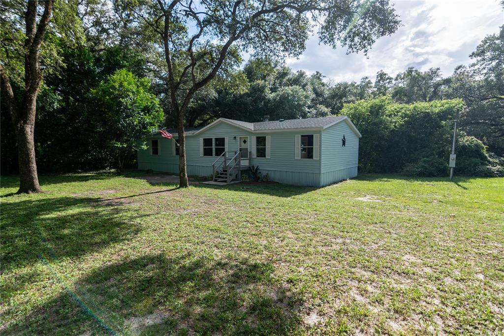 Remodeled ..Turn Key... Move-In Ready Fleetwood Homes, Harbor Springs Model, 4 Bedroom, 2 Bath, 1,560 Square Feet of open living area located on a very private country setting in Zephyrhills on 1.56 Acre (165 x 413) lot.  Honey Oak waterproof/scratch resistant Laminate Floors flow throughout the home highlighted by 5 ¼ baseboards. New carpet and pad in bedrooms. The Chef's kitchen has beautiful Custom-Crafted White Cabinets with quiet close drawers and doors. The Cabinets are adorned with Sierra White Granite Counter Tops with a beveled and polished edge. Huge center island offering a ton of storage. Brand New Frigidaire Clean Steel (Smudge-Proof) appliance package offering 1 year manufactures warranty.  Real wood-burning fireplace with stacked stone. Large Master suite with Grey double vanity and tiled shower. . 2nd and 3rd bedrooms are ample sized and share a bath with new vanity and whisper grey shower tile. Freshly textured and painted inside. Both front and rear porches painted.  All new doors, hardware, toilets, energy-efficient LED lights, fans & plumbing. BRAND NEW 30 year Dimensional Shingle roof just installed.  Energy-efficient Goodman 3 Ton AC, new water heater & softener, DEEP well with submersible pump, drop pipe, and water tank.  Septic system JUST emptied and inspected.  NO CDD –NO HOA.