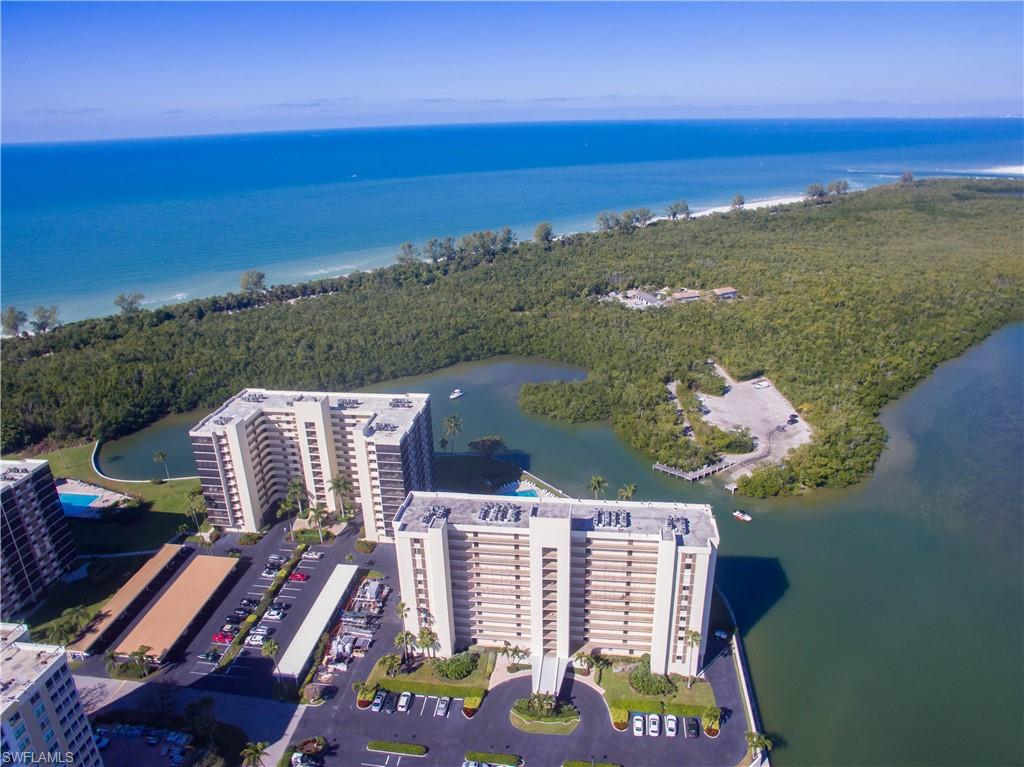 Spectacular GULF & Bay views from this 2 bed 2 bath condo! Enjoy beautiful sunsets over the gulf and manatees and dolphins playing in the bay. This unit has hard surface floors throughout, granite counters & newer cabinets in kitchen and baths. Residence also has newer electric Hurricane shutters and impact windows for your peace of mind while away. This community has it all, minutes from one of the worlds finest beaches, a large pool, tennis court, pickleball,  bocce, a marina with docks and kayak spaces to lease plus a community room on the bay to meet new friends. As if this isn't enough Surf Colony is only minutes to the Ritz, Mercato, Trader Joe's and an almost endless amount of shopping dinning and entertainment venues.