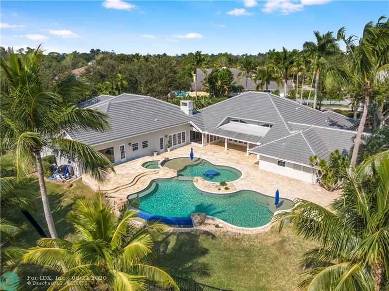 Luxurious waterfront estate framed by lush tropical landscaping. Expansive water views from almost every rm & multiple doorways integrate indoor & outdoor living spaces. The luminous open floor plan & vol. ceilings are conducive to today's lifestyle. The culinary kitchen with upgraded appliances opens onto the family rm featuring a gas fireplace. The oversized media/game rm is also equipped with a 2nd full size kitchen. Additional details include a professional fitness rm, sports court, office, & lavish master suite. The oversized infinity edge pool, spa & patio area are complimented by a fully equipped summer kitchen, covered loggia, wet bar & multiple televisions. Guard house entry & 5 star amenities. Owner financing available.  SQ FT per seller's appraisal.