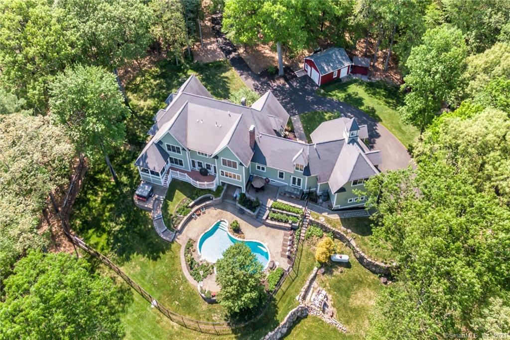 Truly Special!! Quietly located in the western Simsbury foothills, this gracious country home has been masterfully expanded and enhanced to create a very special oasis! Exquisite landscaping with almost 6 acres surrounds this residence that enjoys views to the east for sunrises, a heated gunite salt water pool, spa with waterfall, bluestone patio, open front porch, a vaulted enclosed porch, stone walls and terraces! A magnificent chef's kitchen with oversized island, honed granite counters, fireplace and high end stainless appliances also has a walk in pantry and expansive windows to capture the outdoor splendor! A sprawling, open floor plan provides the perfect atmosphere for entertaining as well as a first floor bedroom/bath wing with inlaw/au pair potential, along with two stairways to the upper level. The pampering master bedroom suite is a serene retreat, while two bedrooms share jack/jill bath, and another with en suite bath, plus there is an expansive media and office wing! Walk out lower level features a warm recreation area with fireplace and bath perfect for after swimming activities! There is a heated 3 car garage that can accommodate a lift plus a detached storage barn. This hidden niche neighborhood enjoys miles of trails that are easily accessed from this property for hiking and a private tennis club is within walking distance. New driveway, generator ready, hardie plank siding, c-vac! Welcome to Simsbury, an award winning town within 2 hours of Boston and NYC!