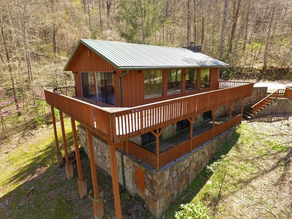 Charming home located off Roaring Fork, less than 1 mile from the Parkway in Gatlinburg. True 1970's solid construction with lots of mountain stone, glass, and wood siding. The home has been gutted to the studs. There is a new roof and new appliances have been purchased. This is a blank canvas and developers dream. Over 900 square feet of outdoor decking and patio space. Property would make a great overnight rental, permanent residence, or a true second home. The property has many mature trees creating a serene and private atmosphere. This home has tons of character and blends into its surroundings. The property offers an additional 11.33 acres at the back of the property that literally borders the Great Smoky Mountains National Park. There are several potential home sites and would make a great rental community. There are many possibilities with this rare Gatlinburg property. Whether you are looking at an investment, development, or purchasing your next home in the Gatlinburg area, do not pass on this one! Drone Photography was utilized in this listing.