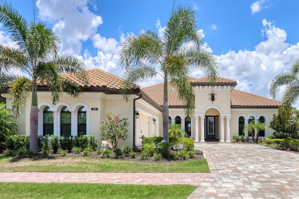 Where your home reflects your style, this gorgeous Cardel custom home is situated on an amazing lake homesite. Country Club East is a prestigious guard-gated neighborhood in Lakewood Ranch. Enjoy the timeless appeal surrounded by the architectural details throughout this masterpiece. The soaring ceilings from 10 to 16-feet give you the grand feeling of true luxury. The engineered wood floors give this home a cozy ambiance. Cook in your very own gourmet kitchen with a 3.5-inch granite floating island and countertop seating. Custom cabinetry, stainless steel farm sink, Sub-Zero and Wolf appliances and a large, adequate, sizable built-in pantry cabinet, along with a large walk-in pantry. Generous dining area to entertain family and friends. An enormous gathering room off the kitchen gives you the most breathtaking view of the pool, spa and water. Pocket sliding doors disappear for a wide-open view of the backyard. There, you will find a massive paver lanai, stone trimmed gas fireplace, complete outdoor summer kitchen and plenty of space for sunning. Outside speakers for your music enjoyment. The owner's retreat offers two colossal walk-in closets with built-ins. The lavish bedroom has a sitting area and picture window. Walk out your bedroom door that leads off to the alluring lap pool. The substantial bath has a walk-in shower, dual sinks, linen and a private water closet. Ample storage everywhere. The secondary bedrooms are considerable in size for guests to be comfortable. Gigantic bonus area that can serve as flex space for an extra bedroom, workout area or media room, which also has another set of sliding doors that lead off to the pool area. A great built-in wet bar and entertainment center. This home also has a generator and impact-resistant glass. Designer plantation shutters, blinds,  draperies, lighting and fans grace this property. Three zoned AC systems and a three-car side-load garage with even more storage. Country Club East has a community pool and a fitn