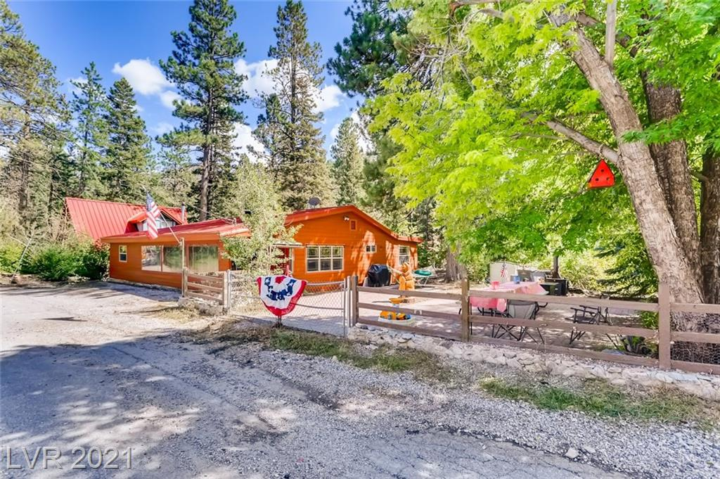 Owned land/not leased land. RARE Double Lot in Old Town Mt. Charleston! Walking distance to school/library/fire dept/trails. Enjoy cool mountain breezes and temps, just minutes from the heart of Las Vegas. One Story, nearly 1900 SF, huge fenced side yard w/shade trees, pavers, flower beds, BBQ, double wide gate, more. Built by a famous southern NV architect. Metal roof, concrete siding, newer deck area, windows, doors. Massive Family room w/vaulted and beamed ceilings, fireplace w/insert, TWO Sun Rooms, front and rear. Soapstone fireplace @ entry. Updated bathrooms. Spacious laundry and storage rooms. 3 bedrooms, 3 living areas. Retro kitchen w/key updates. Fun lighting and flooring throughout. Mountain Views. Perfect getaway or primary home. Septic Tank inspected/serviced/certified. Lowest price psf on the mountain at just $253 per sq ft---AND includes a double lot!