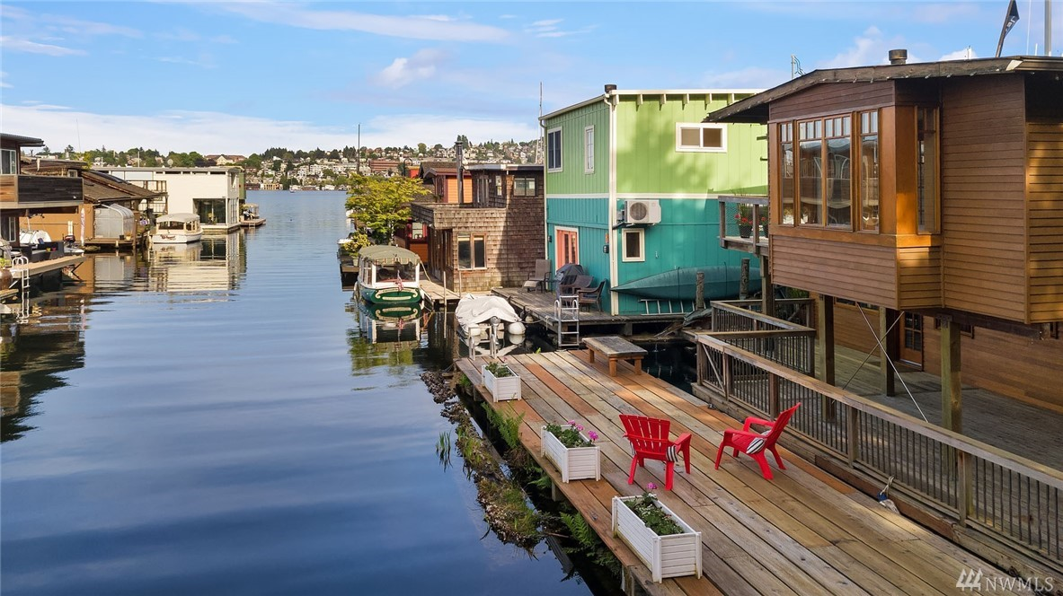 """Spacious and light 1840 sf custom designed NW Craftsman floating home. 1190 sf of exterior decks, three on upper level + an 11x40' auxiliary  float and two boat slips! Owners had a 40' sailboat at their doorstep. Reverse floor plan with open upper living spaces. Open beamed ceilings with 9 sets of divided light French doors framing the lake & channel views. Clear fir millwork, built-ins, and wood floors throughout. Co-op dock next to bike trail & city pocket park. On """"Sleepless in Seattle"""" dock."""