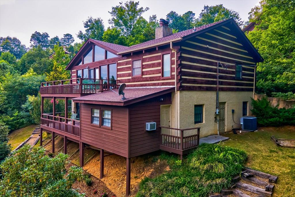 Unobstructed views of the Smoky Mountains. What everyone asks for, but so hard to find! Well-maintained Log home located on a very private gated and oversized lot in the beautiful mountain community of Cobbly Nob.  Enter to the community through golf course and then just a short dr (and not far up the mountain) to extraordinary views and privacy!  The grounds have an abundance of landscaping with private sitting area to take in the views and area for horse shoes and outside activities, all surrounded by lush landscapes.  Upon entering the home, there are extraordinary views that can be seen through a wall of glass all across the back of the home out to the deck (on both levels). Vaulted ceiling, wood interior, open great room concept, and kitchen cabinets to hold enough food for an army! Fireplace with stone from floor to ceiling and Master bedroom is on main level.  Lower level has large Family Room/Rec Room, with another stone Fireplace, and more bedrooms and more views!  So many log homes in our area are built for rentals only, however, this is perfect for permanent or second home, with lots of space and extra storage and walk-in closets. But be prepared, the views will make you fall in love with this one! (Exclusions to contents. List in associated docs.) Drone pics has been used.