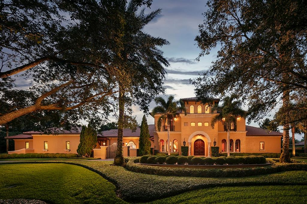 Nestled on more than an acre within the private guard-gated community of Isleworth, this extraordinary custom golf-front estate offers exquisite living in the heart of one of the finest golf club communities in the world. Built by leading custom home builder Pellegrini Homes, this stunning Italian masterpiece spans more than 7,100 square feet with lavish detail, impeccable resort-style grounds and plenty of privacy creating a golf-front haven. Beautifully handcrafted cypress grand entrance doors reveal a gracious, open interior featuring custom stone columns, broken-edge Castle tile and a curved, floating staircase. The roof is fully custom with natural terra-cotta tile imported from Colombia, and all of the interior walls are faux, Venetian plaster or trompe l'oeil. From the formal living room with soaring windows framing the tropical pool and grounds to the dining room enrobed in deep red Venetian plaster, the curated interiors were thoughtfully planned to feature custom complementary finishes while offering views of an arch from every angle. An unparalleled venue for indoor-outdoor entertaining, the main gathering area within the home comprises the luxurious custom kitchen featuring a copper ceiling, professional Viking appliances and a large walk-in pantry together with the family room and built-in bar designed after a five-star hotel bar. Oversized hurricane-grade sliding glass doors can be fully pocketed to unite the interior with the expansive screened lanai featuring a large television, fireplace and custom full-size grill outfitted with dual burners, a Viking commercial hood and heat lamps. The estate boasts four en-suite bedrooms including the spacious owner's retreat which offers a peaceful sitting area and a stunning custom bath featuring Kohler's massive RiverBath circular tub, dual vanities, a large walk-in shower, two water closets and a spacious wardrobe with island, cherry built-ins and a second washer and dryer. Unique living spaces within the home