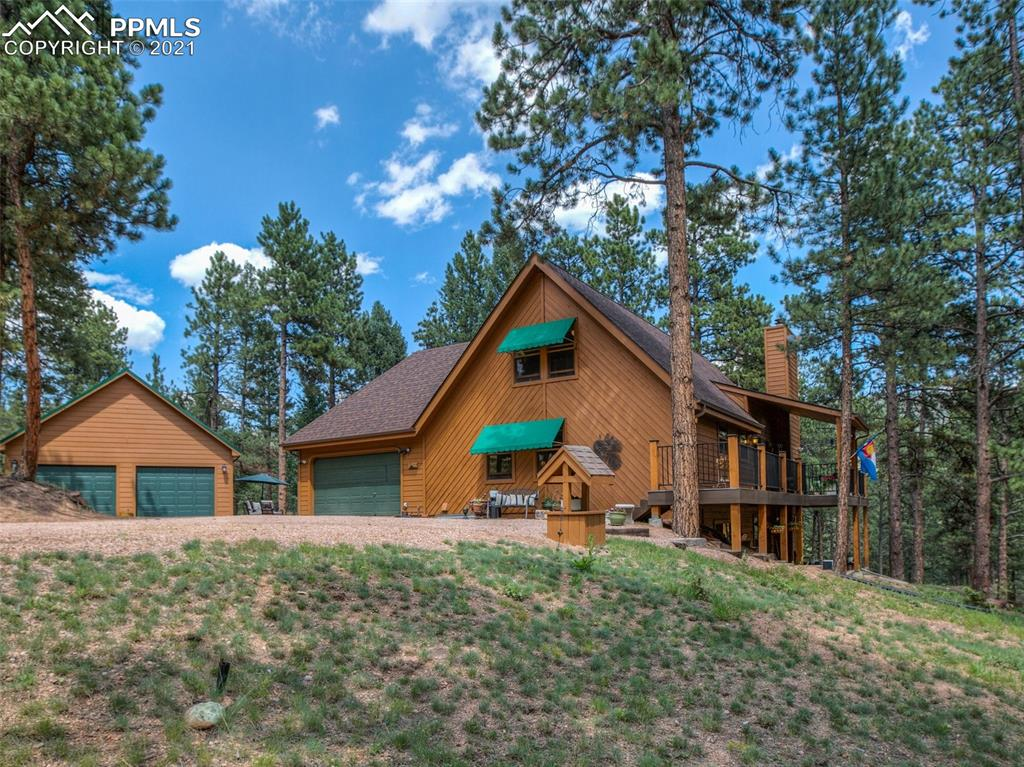 Discover your destiny and new mountain lifestyle in this rustic and immaculate home on 5.68 acres surrounded by mature pine trees. Vaulted ceilings and large picture windows greet you on the main level, and topped off with a cozy wood burning fireplace & dining room that allow friends to come together in the open floor plan. The updated kitchen features new hickory cabinets, stainless steel appliances and keeps the chef engaged with guests in the living room and dining room. From the main level you and your guests will enjoy the outdoors on a new composite deck. The owners suite is located on the main level along with a guest bedroom; both served by a 5 piece bathroom. The office area over looks the living room, and offers great views. The upper level has a loft bedroom. The lower level offers a newly remodeled family room, custom wet bar, with a beautiful gas fireplace, another bedroom with an updated ensuite. The lower level is your access to the concrete patio for outdoor entertaining, and the large yard for your pets and family members. Bring your R/V, trailers, and toys as this property has plenty of room. The 24× 24 detached garage is not just built to store  but is also perfect for indoor/outdoor entertaining as it has in-floor radiant heating, custom designed corner windows built from an overhead garage door, and a concrete patio.  Perched on a quiet wooded cul-de-sac this home feels like a remote lodge, but is located minutes from Woodland Park, and only 30 minutes from Colorado Springs. National Forest, mountain reservoirs, state parks, are all just minutes away for your weekend adventures. Skiing at Breckenridge is just under 2 hrs away. Make this your home in the mountains today!