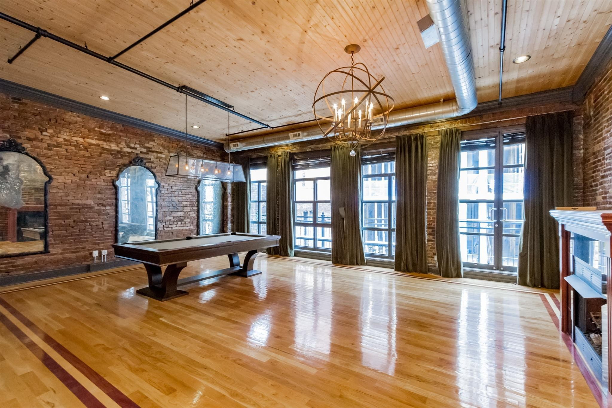 Stunning rare 3183 sq ft penthouse plus 600 sq ft rooftop terrace, views of Nissan Stadium, Ascend Amphitheater, Printers Alley & Batman Building. Nothing like it in the city. 2 fireplaces, exposed brick, original beams, hardwoods & granite, Chef's Kitchen with gas cooking. Restored building in historic district. Attached garage parking for multiple cars & private entry w/ elevator to penthouse. Live in the heart of Nashville. Rentable; Short Term not currently allowed but up for HOA vote soon.