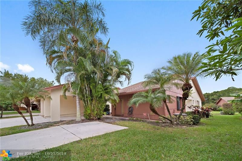 Nestled within the quaint community of Hammocks at Coconut Creek with its park like settings you will find this exquisitely maintained and updated split 2-Bed/2-Bath villa on a lushly landscaped lot. Living areas with contemporary appeal: ceramic flooring throughout,  kitchen lined with white & teal cabinets, copper fixtures, farmhouse sink, and sparkling white appliances. Spacious great room with slider leading to the patio, dining area and solarium to the rear for your enjoyment. The grand master suite is bright with updated cabinetry in the bathroom. Hammocks at Coconut Creek dues include: common areas maintenance, lawn care, pool, and exterior paint. This outstanding home is in move in condition, schedule a tour today.