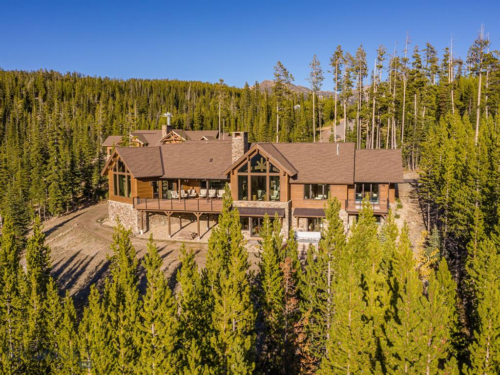"""This is the ski-in/ski-out gem that you have been waiting for! Offered fully furnished (with few exceptions), allowing you to move in with little more than a suitcase! This new custom home built by Blue Ribbon Builders is a perfect balance of refined and rustic: Elegant with clean lines, reclaimed wood accents and perfectly proportioned rooms. Stunning chiseled edge travertine flooring. Solid walnut cabinets, solid Black Walnut flooring, solid granite counters in kitchen and dining area, marble and tile baths. Huge views of Lone and Fan Mountains. Wolf and Sub-Zero appliances. State-of-the-art home theatre. Recording studio. Full Crestron home automation system with interior and exterior security cameras and four separate networks. Radiant heat throughout, including garage. Expansive outdoor living areas with fireplace, overhead radiant heaters, TV and hot tub for 7 people. Ski room with lockers, boot heaters, double stacked laundry. Family room has game computer with 75"""" monitor."""