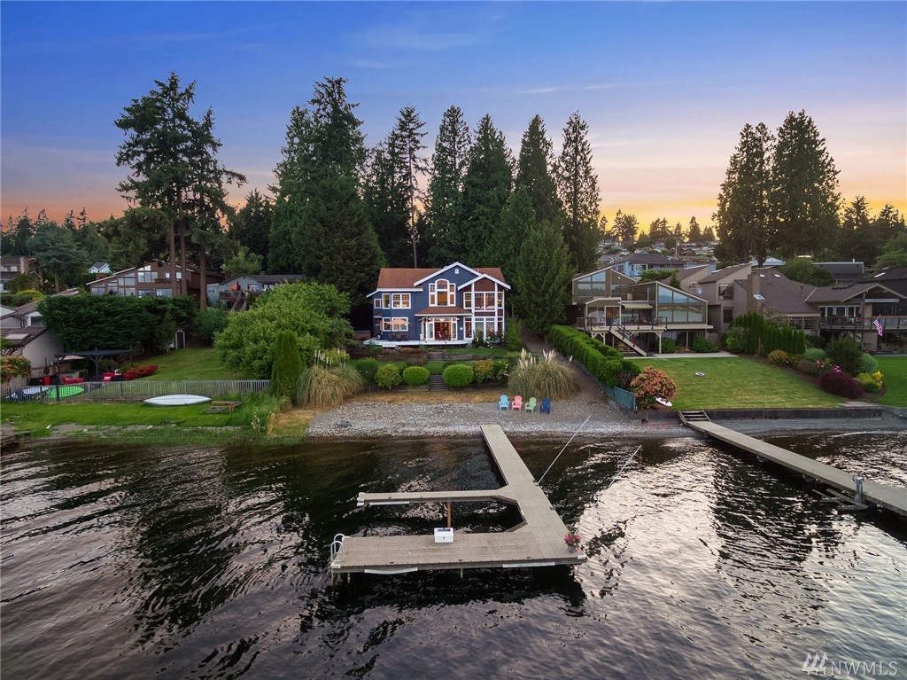Space, Privacy, View, Convenience! Custom home on rare 75' no-bank waterfront half-acre, close-in to Bellevue, Seattle & Sea-Tac. Park-like upper lot precedes the vaulted entry.  Inside, slate & tigerwood floors lead to panoramic lake views. Gourmet kitchen with one-piece 10' island & new high-end appliances. 3 ½ Bedrooms + loft. 3+ Bath. Dedicated Theatre/Music Room & Library. Garage includes workout/shop area. Private beach, Dock, Boatlift, Boat Shed & Hot tub.  Award-winning Bellevue schools.