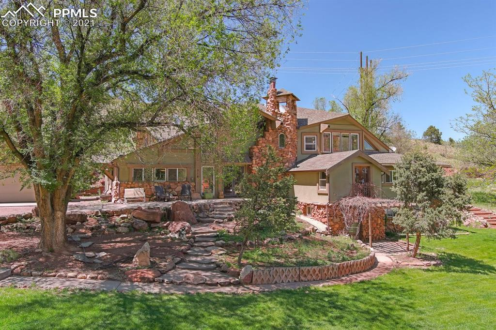 Don't miss this rare opportunity to find a large home on almost 2 acres in Manitou Springs! Nestled in a hidden valley, this home is conveniently located near the high school and the Intemann Trail. With only a few neighbors on a private driveway, the setting is serene. Rarely will you find a front yard as large and lush as this one - perfect for yard games and entertaining. The primary bedroom has an attached office and a quiet sitting room with a walk-out deck. There are THREE separate living room spaces - just think of the possibilities! The main office is centrally located in the home and has great lighting and plenty of room for puzzles and board games. With easy access to the spacious 3-car garage, the mud room/8th bedroom has it's own entrance and an attached full bathroom. The renovations done to this unique property include cherry cabinets, granite counters, Viking stove, double ovens, 2 furnaces, 2 air conditioners, a theater room, a large stone fireplace, newer stucco, newer roof, new carpet and kitchen flooring, newer paint, vinyl windows, tons of built-ins, and a fun wine cellar! There is also a separate 504 square foot 1 bedroom, 1 bathroom apartment complete with a living room, kitchenette/dining area, and separate entrance, perfect for guests or added income. Beautiful Garden of the Gods and mountain views! This is truly a one-of-a-kind property in a beloved one-of-a-kind town. PRE-INSPECTED!
