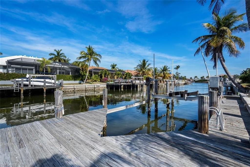 "Is it time to enjoy a laid back, tropical lifestyle where you live in ""Vacation Mode"" every day? Marco Island is home to some of the world's most beautiful beaches and offers access to both the Gulf of Mexico and the mangrove-lined estuaries of the Ten Thousand Islands. Take advantage of this great opportunity to own a PRIME WATERFRONT PROPERTY with a boat lift and EASY ACCESS TO THE GULF (just one bridge). With vaulted ceilings and a split floor plan, this home is ready for your personal decorative touch and updating.  Outdoors you'll find a spacious covered and screened lanai that overlooks the hot tub and 60' POOL designed for SWIMMING LAPS. The roof was replaced in 2018 and the property also features a rare, WALK-OUT BASEMENT that is ideal for a workshop, extra storage, etc. Don't miss this opportunity for a residence with great potential! Property is being sold ""As-Is"" with right to inspect."