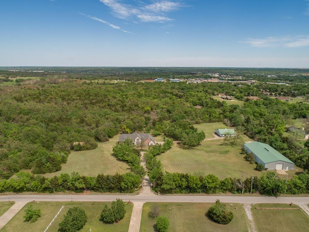 Rare find--absolutely amazing 10 acre estate in the city! Horse Stables w/5 Rockin J stalls, 2 offices & half bath. 60'x120' (7200 sq ft) building w/kitchen, 6 offices, 2 baths, generator, car lift & RV overhead door! Competitive sand volleyball court built in 2016! Well for shop & sprinkler. Security w/camera surveillance. Gorgeous pool w/hot tub & stunning waterfall! Large backyard deck w/outdoor shower perfect for year round entertaining! During extensive landscaping a piece of history was discovered--charming settler's house! Handsome study w/bookcases, wood floors & plantation shutters.  Family room w/wood floors, wood beam ceiling & wood burning fireplace. Master suite w/crown, door to deck, speakers & walk-in w/cedar lined safe room. Master bath w/whirlpool tub, walk-in shower, his/hers granite vanities & plantation shutters. Gourmet kitchen w/walk-in pantry, island, granite, double ovens, 6-burner gas cooktop, ice maker & sub zero fridge & freezer. 3 beds/2 baths/game room up.