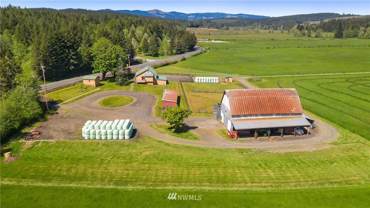 RARE one-of-a-kind remodeled farmhouse nestled in the foothills amongst year-round Bunker Creek on a sprawling 127+ acres! Kick your boots up and enjoy the peaceful valley setting before hay season starts while admiring surrounding marketable timber, spring-fed pond, and level pasture grounds. Bring your livestock with you - this property is fenced and cross-fenced along with several outbuildings including a historically registered barn, machine shed, and loafing shed with hay storage. Cross your own wooden bridge to access another potential building site on separate parcel where a mature orchard rests from original homesteaders. 5 parcels included in sale. 10 mins to Adna schools and easy I-5 access.