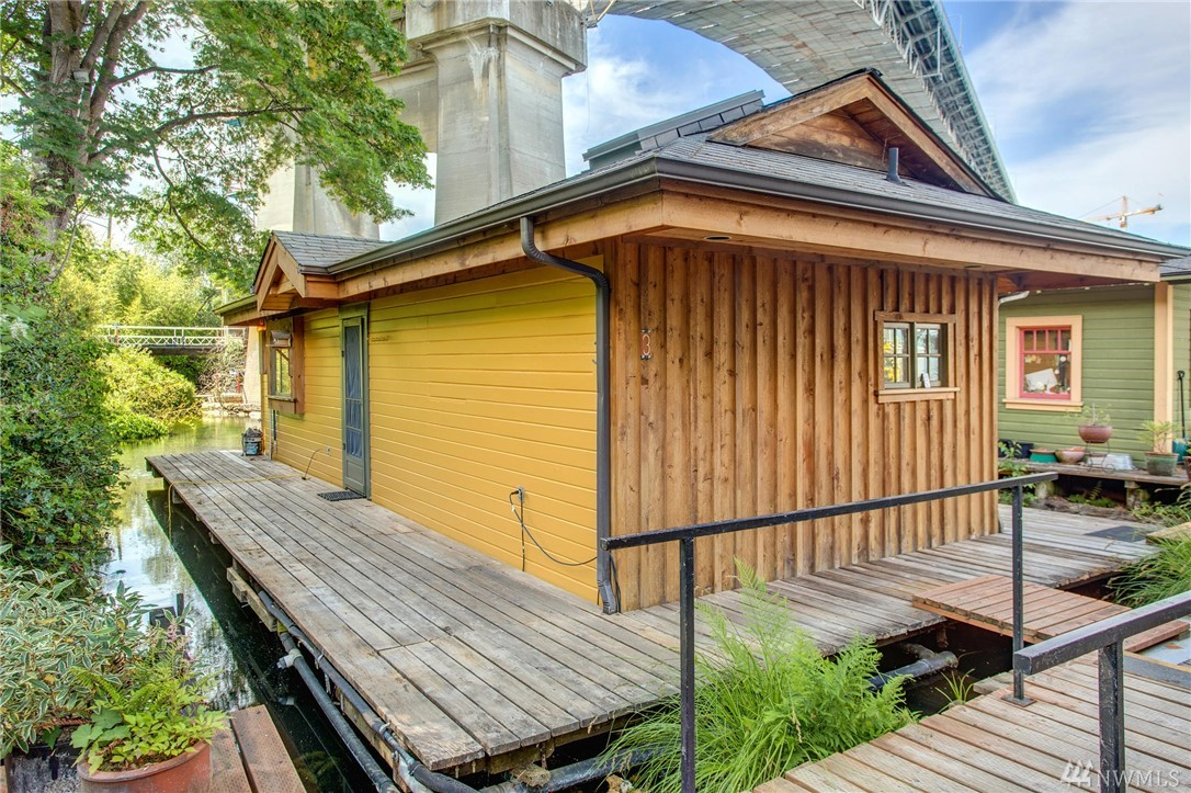 Extremely well done old- style Seattle houseboat with timber style construction, custom fir beams and ceiling, approximately 11 feet to the ridge beam, condominium-owned moorage, sweet westerly views, moorage for a 20' boat, sky-lights, original cedar siding with fresh paint, custom shoji screens separate living spaces, dog friendly dock, built in bench near front door, zone 25 permitted parking for two spaces plus guest pass and a short walk to Fremont and on the Cheshiahud  bike trail