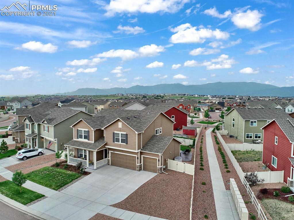 You will not want to miss this beautiful home on a prime lot and location in The Trails at High Forest Meadows. The location can't be beat with a 2 block walk to the school nearby - Grand Peak Academy, and lovely Park.  More than a Peek-a- boo view of the Front Range from your beautiful  spacious yard and stamped wrap around concrete patio. The backyard is totally fenced in and private.  This home has lots of curb appeal with an adorable front porch with space to enjoy a get away or cool summer drink. This 3 Bedroom home has a  bonus Loft space for office, study,  seperate TV area, or as is currently being used as an amazing craft room. Enter in and feel immediately welcomed. The front , main level office has beautiful french doors and lots of space. The Kitchen is open to the Dining area and Living Room. The center island, pantry, counter space and storage are added features that will make you want to call this one HOME. You are able to walkout to the beautiful backyard for extended entertaining, Colorado sunshine, and mountain views. The 3 car garage is a dream for all the toys and tools. This lovely home has higher ceilings, neutral color scheme, and a functional floor plan. Pride of ownership shines here! This quiet neighborhood is tucked away from it all but close to shopping, entertainment, great schools, and a walking trail system/path throughout the lovely neighborhoods. Book a showing today!