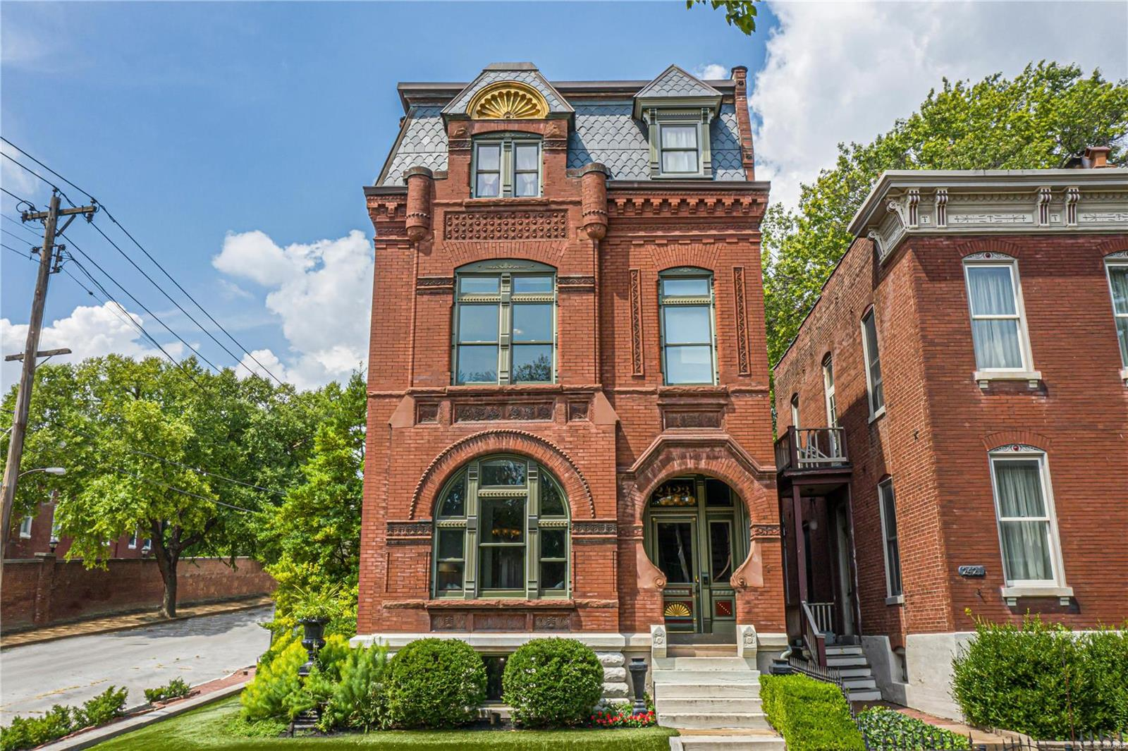 """Known as """"The Keyhole House"""" for its uniquely shaped entry, this 4,609 sq. ft., 4 bedroom, 3 bath home was built in 1890 by its original owner, Michael Reinagel, the city's premier brick mason of the 1800s. A true work of art - the home features more styles of ornamental brick, sandstone, and terra cotta than any other residence in St. Louis. Over the past 24 years, the home has been carefully curated & lovingly renovated, with attention paid to every detail. The spacious, modern 30' x 14' kitchen features a 36"""" Wolf range, premium KitchenAid appliances, honed granite countertops, 16 sets of drawers, 45 cabinets & iridescent stained glass tile. The 2nd-floor master suite features oversized dual closets, a gas fireplace, laundry room, and private bath with a spacious custom glass shower & premium Kohler fixtures. The backyard has a deck, a brick patio, and an English boxwood garden, elegantly framed by a 9' custom lattice fence. There's even a 3-car garage for your vehicles."""