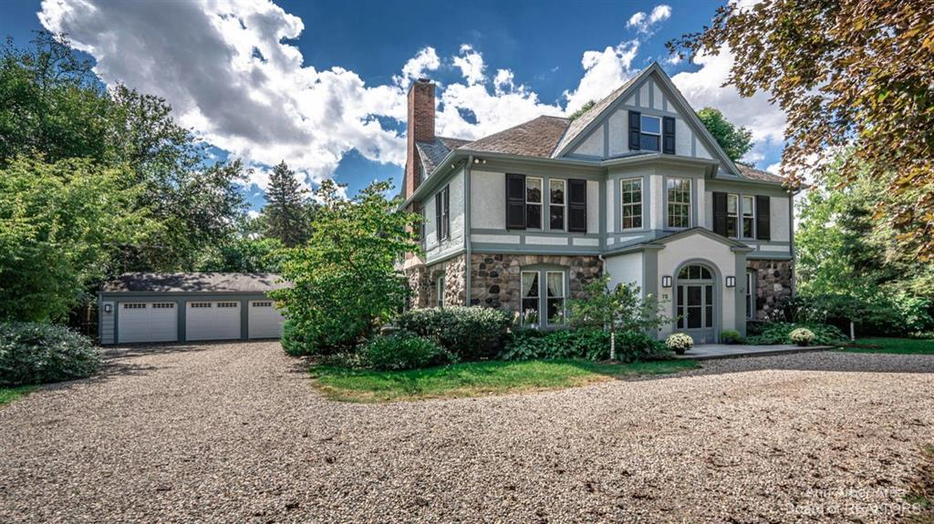 This is one of the most Grand and Spectacular properties in Ann Arbor. This historic, 3 story home rests on 5.68 acres with panoramic views of the Huron River.  The property is simply breathtaking with mature trees and gorgeous grounds. The bluff-top water view will be incredible with trees cleared. The home was moved to this site in 1936 by the Earhart Family from what is now the Concordia College site. It is loaded with all the charm and craftsmanship of the era with significant trim detail, hardwood floors, and many fine architectural details throughout. Highlights include a welcoming foyer with expansive staircase and barrel ceiling hall, spacious living room with fireplace, stately den with built-in bookcase, modest kitchen with eating area, formal dining room, screened porch, and great back hall mudroom. The 2nd floor includes a modern primary bedroom suite with large bedroom area, walk-in closet, and attached bath, 2nd bedroom with private bath, and 3rd and 4th bedrooms with sha