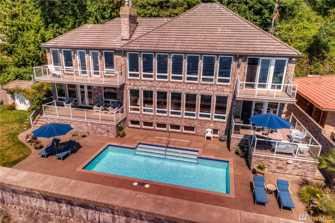 Sweeping views from this exceptional home with 150' of Puget Sound waterfront at your doorstep. Built to enjoy the seascape & capture the Olympic Mountains, this custom home with over 6,000sf of living space features private boat ramp, outdoor pool, gated street & second residence. Luxury abounds inside with soaring ceilings, hardwoods, travertine tile, open floor plan & main floor master. Floor to ceiling windows capture the stunning views from almost every room. Waterfront living at it's best!