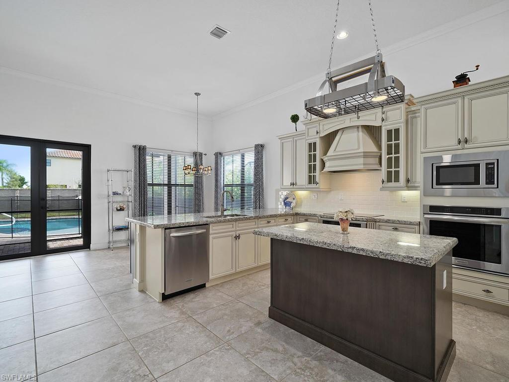 """H.13440 - Entertainer's delight!  This 4/3, """"Briones Model"""" with over $130,000 in upgrades is a rare gem!  Single story, 2 car side entry garage with a private heated pool/spa (tanning ledge/ sun shelf in pool) with a privacy wall.  A chef's dream! High-end upgraded kitchen with 42"""" inch wood cabinets w/rope crown molding, granite countertops, backsplash, under-lighting, pot rack over island, and extra storage (under cabinets) in kitchen.  Porcelain tile in living area, crown molding throughout, window treatments, garage door opener keypad & upgraded faucets throughout (Moen & Kohler). Upgraded washer/dryer with cabinets storage and laundry room sink. Stunning Master bedroom upgrades include custom closets, plantation shutters, frameless shower, tile to ceiling in shower, upgraded wood vanity cabinets, large soaking tub and porcelain plank tile. This gorgeous and lovingly maintained home is walking distance to Town Center, dining, Publix, Ave Maria amenities, playgrounds, parks, walking/jogging trails, dog park, fitness center, tennis courts, bocce and more.  Come experience this one of a kind home in Ave Maria's award-winning neighborhood Maple Ridge. New Club House!"""