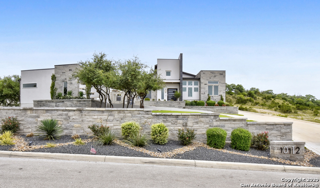 This extraordinary, contemporary estate located in one of the city's most prestigious communities, The Canyons at Scenic Loop, was custom designed to take advantage of breathtaking Hill Country views for miles.  Located on a remarkably private lot with a uniquely level backyard, this home was built for entertaining with a free-flowing interior/exterior.  With the touch of a button, the entire home is ready for impressive entertaining or easy everyday living - all lights turn on, doors unlock, the blinds open, & music, movies, and fire features are all engaged.  With one more switch, the home readies itself for retiring for the night through impressive Magnolia installed whole home automation.  The entire home can be controlled from your phone or ipad.  Sophisticated and spacious, this contemporary estate boasts an open floor plan bathed in filtered, natural light.  The beautifully appointed kitchen features sleek custom cabinetry, Bertazzoni appliances, double ovens, a warming drawer, icemaker, an entertainers island, custom wine storage, and a walk-in pantry.     The owner's retreat enjoys breathtaking views from every angle, outdoor access, & a spacious sitting area.  Sleek materials enhance the clean, contemporary lines of the master bathroom featuring separate his/hers vanities with custom backlit mirrors, a freestanding tub, glass-free shower w/rainhead, & custom designed, walk-in closet.  The outdoor oasis enjoys an oversized covered patio, outdoor kitchen, TV, fire features, a sparkling pool with stunning spillover edge, & an alluring spa with close proximity to the master.  Complete child safety fence for pool.  On the main floor, enjoy a spacious en suite guest bedroom, a second entertaining space off the kitchen, and a media/gameroom with projector, screen, and 9.2 surround sound.  Executive study with custom built-ins.  The piano room is perfect for welcoming guests.  The spacious casita, currently used as a private gym, features hardwood floors, a well a