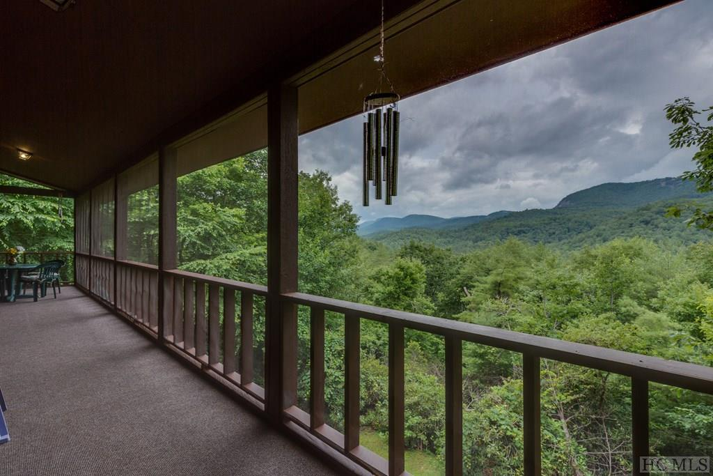 Amazing views!! Acreage!! Privacy,!! No HOA!!! and approximately 5-7 minutes to downtown Highlands!! This house is one of those hidden gems off the beaten path. Once you turn down the paved driveway, you are surrounded by lush foliage on either side leading to your private retreat. Not only will you get 7.78 acres with year-round panoramic views of Brushy Face, and Satullah Mountain, but you will also get a 4 bedroom, 3 bath log home that is ready for you to add your personal touches to update. With 3 stories, there is space for everyone. There are 2 stone wood-burning fireplaces, one in the kitchen and one in the living room, and a wood-burning stove in the basement. You will find the kitchen, living room, bedroom, bath, and laundry on the main floor, with a screened-in porch off of the living room where you can sit and watch the beautiful sunsets, and forget all your worries. Upstairs, there are 3 bedrooms and 2 baths. Downstairs is a recreation /game room, an office, and a large storage area. This home offers privacy, yet close to downtown Highlands with all of its offerings of award-winning restaurants, hotels and spa, concerts at the park, upscale shopping, art museum, theatre, as well as numerous hiking trails and waterfalls. Truly a bargain! For investors, the 7.78 used to be subdivided and could possibly be resubdivdied into 10 lots . This summer house has been  encapsulated, and the exterior was recently painted.