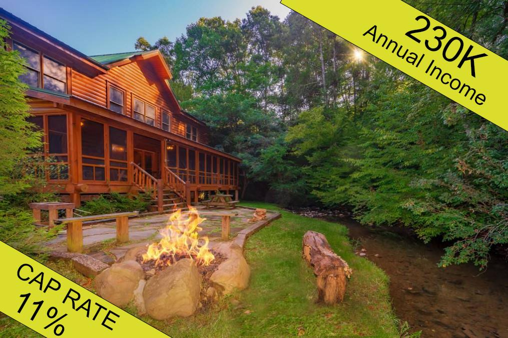 """Creekside Getaway is projected to finish 2021 at $230,000 in gross overnight rental income.  After expenses, this gold mine represents an 11% cap rate for most investors!  With nearly 4,000 sq ft of deluxe accommodations, featuring 8-bedrooms and 8-baths on the gorgeous year-round Caney Creek, this property borders the Great Smoky Mountains National Park.  While it certainly feels like you're miles from the action, the cabin is just 4 minutes from the Pigeon Forge strip and 7 minutes from downtown Gatlinburg.  The owners recently had all-new high-durability floors installed that complement the custom mountain furniture.  This property is truly turnkey all the way down to the knives and forks.  The bedrooms are outfitted to maximize occupancy, each with its own ensuite bathroom appointed with granite vanities, tiled showers, and jet tubs.  5 of the bedrooms are set up with hand-crafted king beds and natural branch futons.  Three rooms feature queen bunks and the same high-quality futons.  The game room comes stocked like a Dave-N-Busters with a pool table, foosball, twin driving arcade games, Big Buck Hunter, and a large screen multicade.  With all of that and the open theater, your guests may never run out of things to do together during their stay.  Of course, it wouldn't be a """"Creekside Getaway"""" without Caney Creek.  The back porch is just feet away from this year-round flowing gem that babbles by creating a truly serene setting.  Hundreds of square feet of semi-enclosed porches, patios, gas and wood fire pits, hot tub, comfortable outside seating, and stonework all face the creek and behind it, the national park for maximum vacation privacy.  It's no use sleeping so many people without the ability to feed them!  This kitchen, with its stainless appliances, twin fridges, and ample seating is ready to deliver huge meals to your eager guests.  They'll love the two, matching natural branch dining sets.  Every detail in this cabin has been carefully considered.  Excep"""