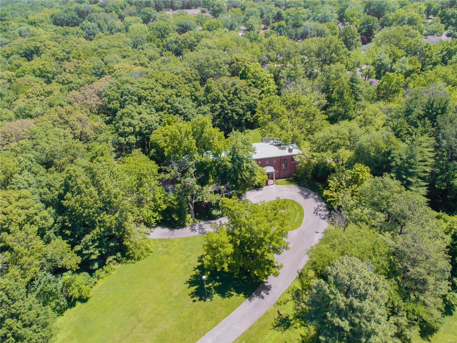 Situated on almost 5 acres in Huntleigh, this property offers privacy and lovely views of the surrounding woods. Substantial home remains on the property that can be renovated. Lot can not be subdivided.