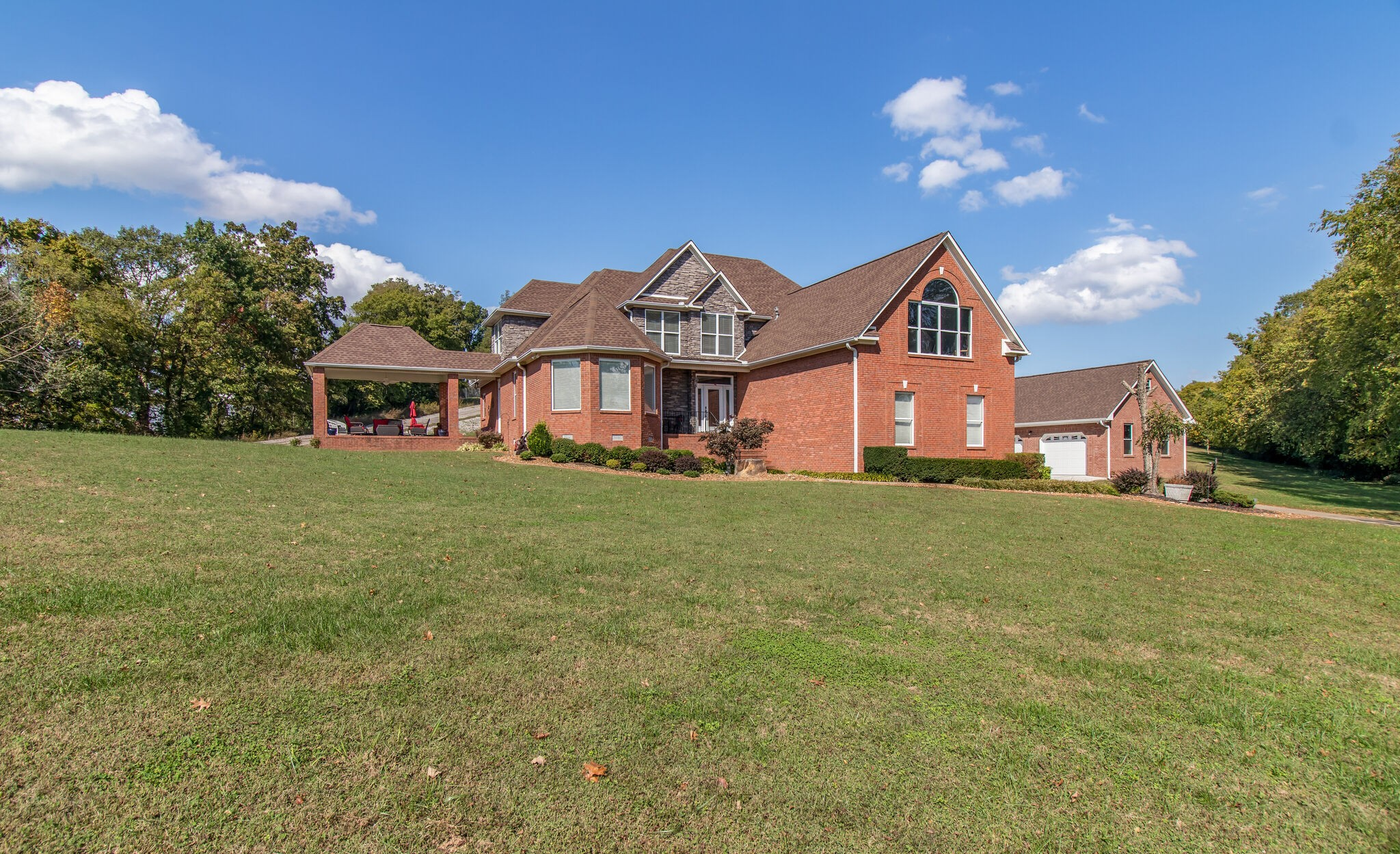 Stunning executive all brick home w/7 acres and in-ground pool perched on a hill with amazing views of TN hills. Percs for 3 bedrooms but has 4. Open floor plan with hardwood floors, granite, custom millwork, ss appliances, 3 covered porches,views from every window, huge bonus room, tons of storage, 3 car attached garage and additional 2 car detatched with unfinished space above,encapsulated crawl space.