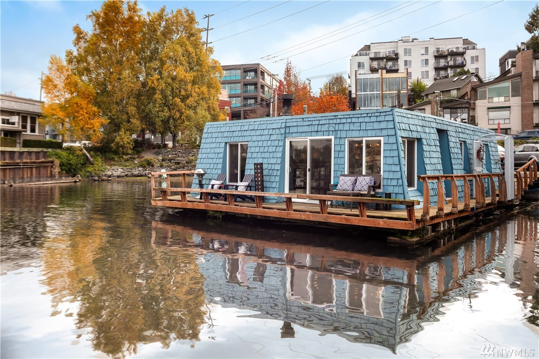 Floating on Lake Union, this blue jewel box in Eastlake is one of Seattle's coolest pads: where the Pac NW lifestyle stylishly combines w/retro cool & industrial chic. Your own gated, private dock leads down to a huge wrap around deck, offering the most envious Seattle setting. Walls of windows & open floor plan allow the party to seamlessly flow from inside to out. A dramatic fireplace, exposed wood beam, barn doors & beautiful hardwoods add the whimsy to complete the ultimate in-city set-up.