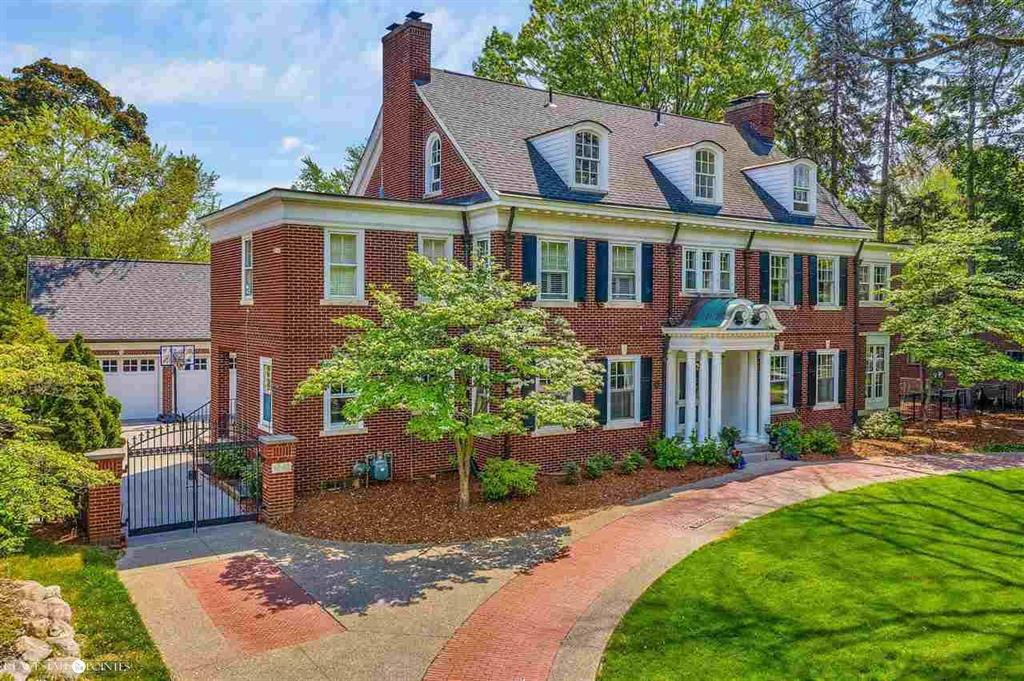 A Grosse Pointe favorite! Historic three-level Georgian Colonial built by George D. Mason near The Village. Formal, center entrance w/ grand staircase. Timeless kitchen w/ stainless steel/wood countertops. New high-end appliances. Eat-in kitchen. Butlers pantry w/ sink. Original steel/marble ice box makes an excellent beverage/bar refrigerator. Large open rooms, high ceilings, wood floors, beautiful moldings, excellent floor plan. Formal living room w/ fireplace. Family room w/ custom built-ins and Pewabic tile floor. Stunning main bedroom suite w/ sitting area, fireplace, new bathroom w/ heated floor. Third floor offers three more bedrooms, office space or guest suite, bathroom and closet plumbed for laundry. Dry, clean basement w/ finished laundry room and multiple storage rooms. New sewer line to the main. Circular brick driveway. Newer, big garage. Extra wide backyard. Enjoy character w/ modern improvements.  See video tour.