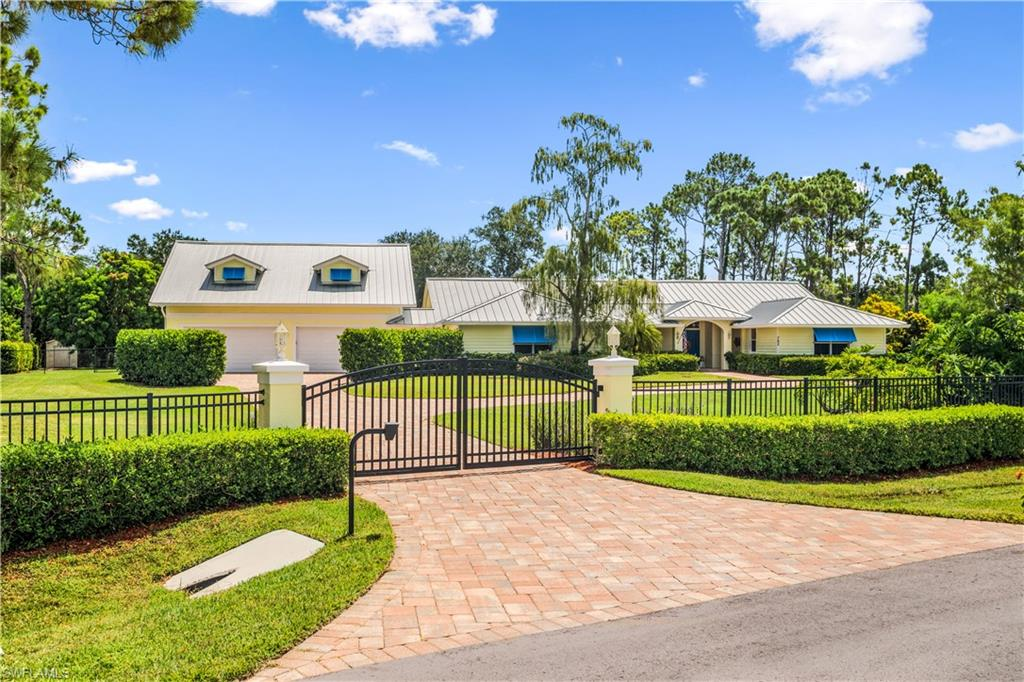 H2932 - This private gated & fenced 1.24 acre estate in Pine Ridge Estates was rebuilt, remodeled and expanded in 2016 to 5832 sq. ft. which includes a 5 car garage, 1200 sq. ft of air conditioned storage, laundry, room, new metal roof, 1 bedroom/1 bath furnished apartment w balcony and private entrance overlooking Lake Bunting. A circular driveway leads to the front of the home which has a nice sized front porch with tongue & groove ceiling.  This home has underground utilities and is on city water with lake fed sprinkler system for landscaping.  The expansive master suite includes 2 master bathrooms, and custom closet. A beautiful 3 way fireplace is centered around the living room, dining room and kitchen  and is a great gathering place. There is a 1,000 gallon propane tank which heats the pool and fireplace and the house is wired for a future generator and dog watch fence.  This home is centrally located and minutes to Mercato, Waterside Shops, dining, entertainment and the beach.  This is a one of a kind property with a beautiful 40 ft. pool and spa on a much desired private lakefront property.  In total 4 bedrooms, den, 4 1/2 baths & storage galore.