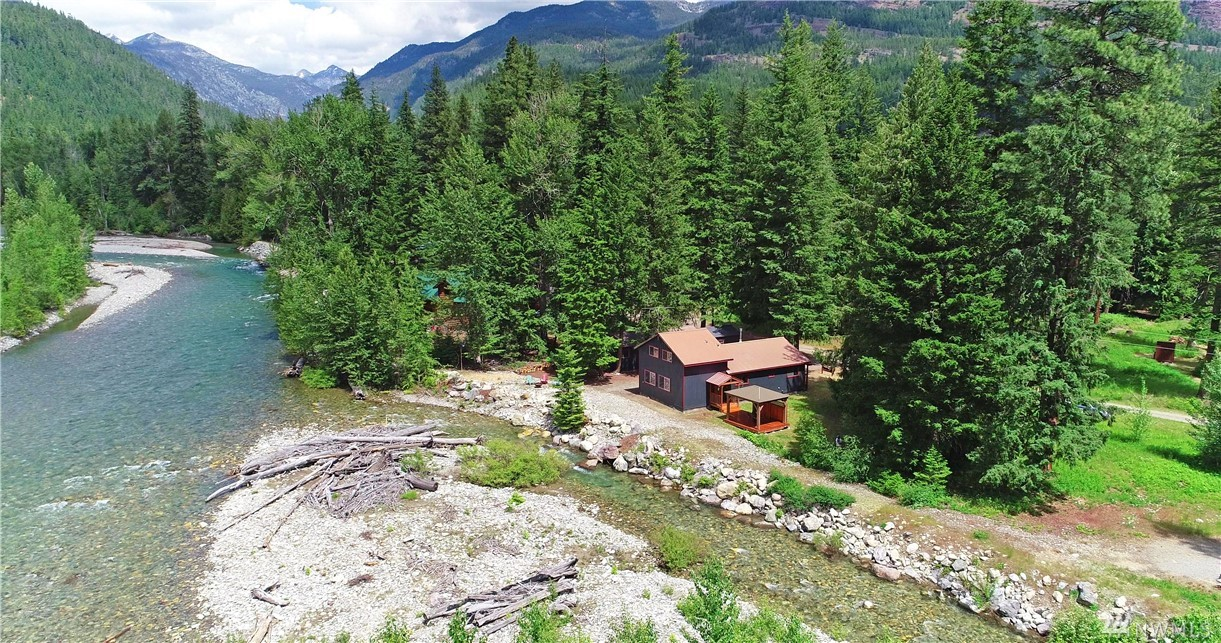 2 Bdrm 1.75 Bth home in popular Lost River on level 1 plus acre expansive, rare and breathtaking riverfront adjacent to Okanogan National Forest. Upgrades include new flooring, bathroom remodels, custom kitchen, covered outdoor deck, and garage. Finished outbuilding provides additional space, storage unit for all those recreation toys, and splendid outdoor spaces to enjoy the beauty that surrounds you in this fantastic location. Low maintenance design for valuable time for what's most important.