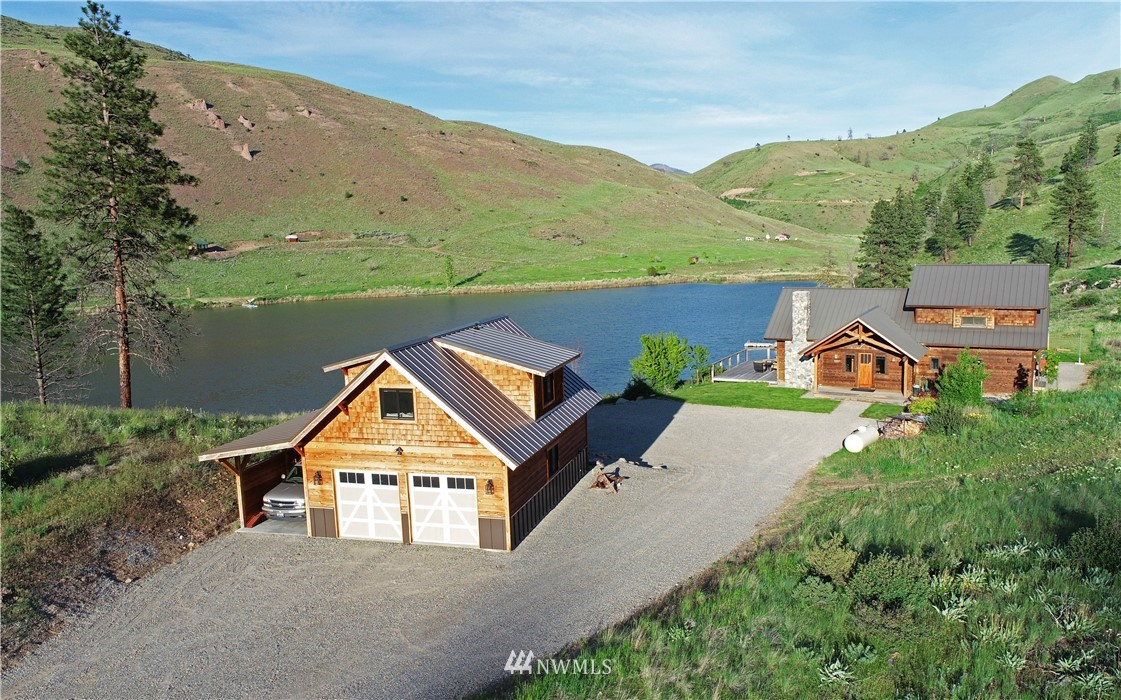 Stunning timber frame home overlooking a serene lake & private dock with 300 feet lakefront!Impressive craftsmanship of intricate beauty & warmth. Sophisticated place of refuge incorporating comfort & efficiency for an active mountain lifestyle. Special features incl  river-rock fireplace, granite kitchen island w prep sink & wine fridge, master suite w deluxe tiled bathrm, 2 guest bdrms w private entries, practical Travertine tile entry, 2nd mudroom/laundry, guest studio above oversized garage.