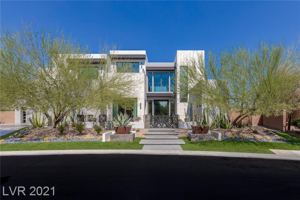 With a contemporary aesthetic that takes full advantage of its stunning view site, this 8,186 square-foot residence in The Ridges epitomizes the grandeur of Las Vegas living. With artistic desert landscaping, tall trees and unique architectural elements add beauty and drama to the exterior. Throughout the interior, natural materials and floor-to-ceiling glass walls capture not only the home's green surroundings but also frame distant vistas of mountains, sunsets, and sky. The primary bedroom suite shares second-floor space with two additional bedrooms, each with an ensuite bath, and a spacious home office for two, with an indoor balcony view of the main level. This extraordinary home has five fireplaces, a four-vehicle garage, a second-floor balcony that spans the entire length of the home, and numerous specialty rooms and features.