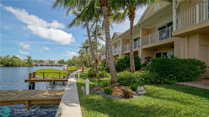 """FLORIDA WATERFRONT LIVING AT ITS FINEST! Exquisite designer-updated corner townhome boasts river & pool views. Open floor plan, gourmet kitchen w/ high-end cabinets, granite and SS appliances, gleaming 20"""" tile, hardwood, newer ac, tank less water heater, front- load w/d, impact windows/balcony & patio sliders. 2nd Floor open landing perfect sitting area/office. Sparkling baths/vanities, M Bath w/double shower glass encl. Dock (up to 22' boat) w/ ocean access, tropical landscaping, covered parking, Two exterior storage closets. Only blocks to Wilton Dr. You''ll love it"""