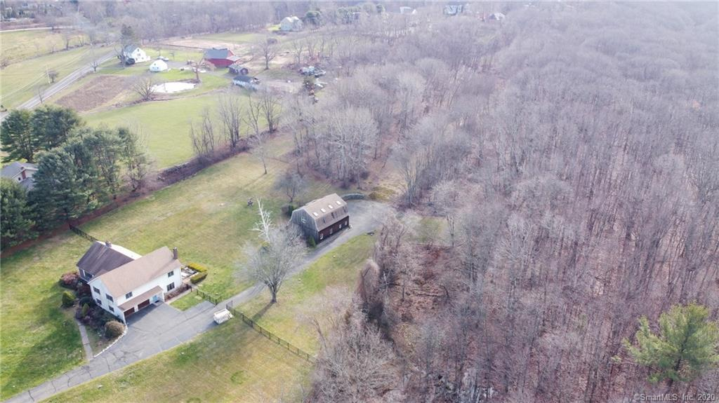 Fantastic opportunity to own this spectacular rolling 9.5+ acre property with two buildings! The setting is absolutely bucolic, situated next to a farm w/horses & bird-watching in abundance. Residence is 2500 sq ft split level home with large den/rec room, fireplaced living room, & 3-bedrooms on upper level; a patio is off the rec room, a deck off the kitchen, an over-sized basement & a 2-car garage with new carriage house styled garage doors. The detached 2600 sq ft barn is the ultimate she-shed/man-cave or entertainment space; perfect for a home office, gym, photo studio, hair salon or many other home conducted occupations. Barn has a kitchenette & full bath, carpeting, loft w/portal style window, center-floor outlets and a picturesque bridge off the second floor.  Current owners bought in 6/20, invested $125,000 in interior/exterior upgrades inclusive of new paint & carpeting, remodeled second floor & guest bathroom, laundry, wainscoating, renovated ceilings, huge double walk-in master bedroom closets, new doors and landscaping plus a 1,000' wrought iron fence that provides plenty of space for kids or fur-babies to play or daydream! Renovations still in process, owners must unexpectedly sell. Come add your finishing touches to make this your own customized sanctuary. Town assessment was $473,400 even prior to renovations. Located near walking and hiking trails (part of the East Coast Greenway), family owned grocery store & shopping. DON'T LET THIS OPPORTUNITY PASS YOU BY!