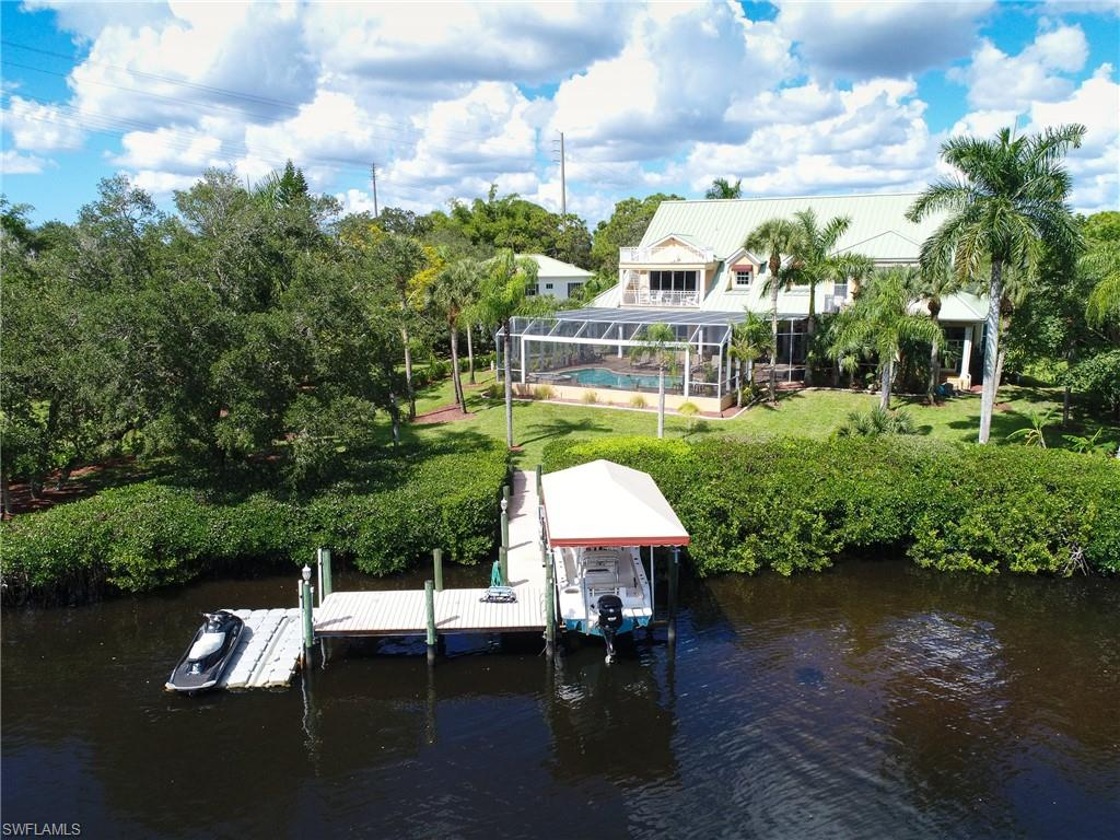 This rare 1.2 acre waterfront property located west is US 41 on the Estero River offers it all: a one owner immaculate custom built home by RG Designs, 5500+ sq ft Living area and 11,000+ sq ft total space of timeless design craftmanship & details, a long driveway past a pond, plenty of yard for gardening pets & children to play, a covered boat dock with lift for boat & jet skis on river with a short ride through beautiful Estero bay to the gulf & a location that is convenient to dining shopping airport and beaches.  Features include large open floor plan four bedrooms, four and a half baths, large office/den, sprawling great room, chefs kitchen, casual & formal dining rooms, piano room, 3 car garage & custom game room with bar.  Hard wood floors throughout, granite countertops, stainless appliances, steam shower, impact windows & doors, volume ceilings, & a metal roof & many large decks & porches with views of river, screened in outdoor living area with fireplace, grill, refrigerator & sink. The large saltwater pool pool/spa offers water features, lighting with a huge lanai overlooking the river.  This hidden gem is in a quite enclave with no traffic or HOA & an amazing setting.