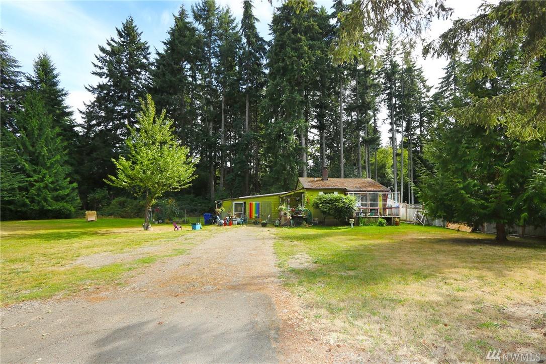 Super affordable; you can't afford to miss this! Level lawns and towering evergreens, home is set well back from the road on almost an acre! You won't find a better location for easy living not far from Vashon's town, bus line, and Seattle ferries. Watch the world go by from the sunny front deck! A fully enclosed back patio is a safe haven for your feline friends and a great place to enjoy views into the forest behind the home. Your creativity can make this the island home you've dreamed about!