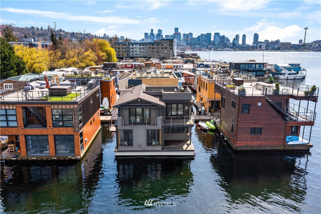Fairview Landing // On one of Lake Union's most desirable docks, this classic two-story with basement craftsman floating home showcases a merging of signature Seattle style with contemporary and elegant finishes throughout. Great room floorplan framed by Nana walls and designer kitchen with full dining room are a chef's delight. Vaulted master suite with built-in closets and step out deck. Panoramic rooftop affords west-facing views from Gasworks Park, to the Olympics, and Seattle Skyline.