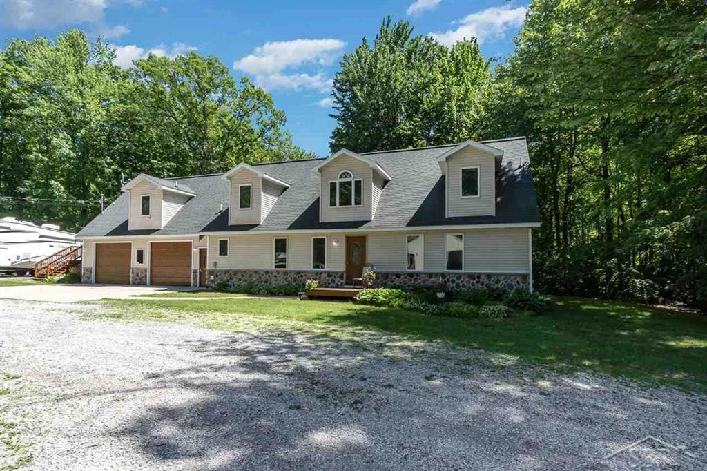 Located in one of the most scenic areas in the Harrison area, this unique home has great curb appeal and sits on over 5 acres. The property features five bedrooms and four full bathrooms.  The kitchen is open to the living areas and the living room, kitchen and dining area are warmed by the glow of a 3-sided gas fireplace.  An abundance of opportunities are present here.  The property is zoned to allow for a home occupation--tons of opportunities utilizing the two large pole barns/workshops.  A studio apartment with separate entrance is also above the garage.  This area could provide a rental income, host guests or be a charming in-law suite.   The 30x40 pole barn has in-floor heat and is currently set up as a workshop and storage.  The newer 30x42 has two 12x42 lean to's for additional storage.  This pole barn is perfect for storage of large campers, boats and recreational vehicles.  Home has many updates in the past year including new flooring and new bathroom.  Must see.