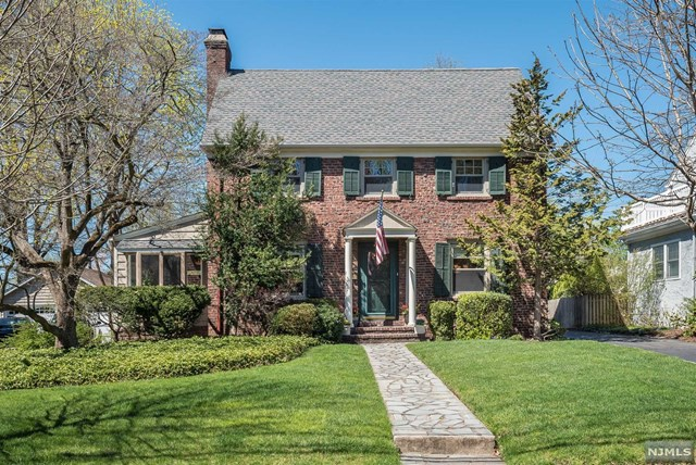 Stately brick colonial nestled on a gorgeous street with welcoming center hall. Gracious front to back living room with wood burning fireplace flanked by French doors opening to a cozy side den w/ brick accent and access to expansive deck. Beautifully renovated kitchen boasts cherry cabinets, granite counters, stunning subway tile backsplash and stainless steel appliances including 6 burner Wolf range. Cheerful kitchen dining area with vaulted ceiling offers a framed view of the beautifully manicured deep yard. Formal dining room, mudroom and full bath complete this level. Second floor presents inviting landing leading to 3 spacious bedrooms including master w/double closet, and updated full bath. Large walk up attic and unfinished basement with high ceilings provide perfect opportunity for additional living space designed to suit your style. Hardwood floors, central air, beautiful deck with black iron accents,  meticulously maintained, just minutes from trains, town, and schools.